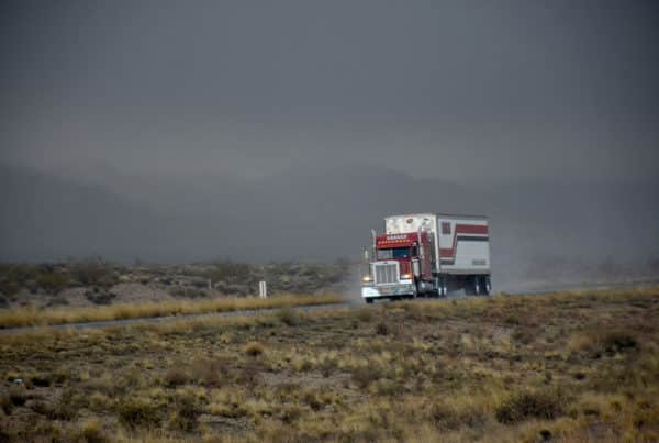 Reefer truck driving down desert highway with mountains in background.